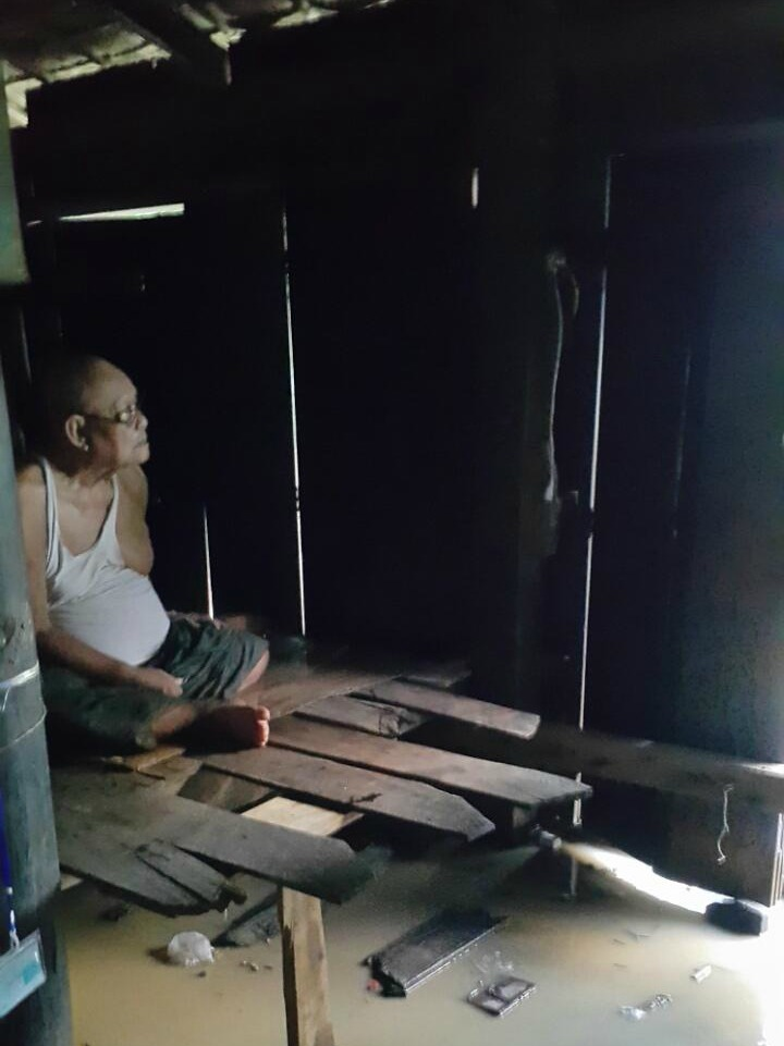 An older person sitting inside a wooden house in Burma